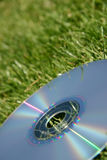 Silver DVD on green grass Royalty Free Stock Photos