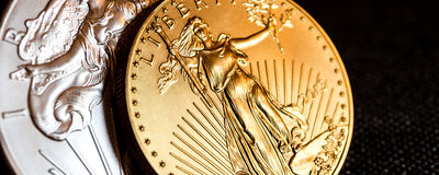 Silver eagle and golden american eagle one ounce coins. Closeup of silver eagle and golden american eagle one ounce coins on black background royalty free stock photography