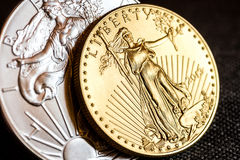 Silver eagle and golden american eagle one ounce coins royalty free stock image