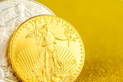 Silver eagle and golden american eagle one ounce coins on golden background stock photos