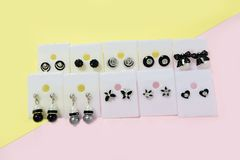 Silver Ear Rings Fashion Accessories. Beautiful Many Pairs of Black and White Earrings Isolated on Pink and Yellow Pastel Backgrou Royalty Free Stock Photography
