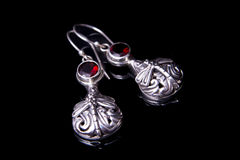 Silver earrings on a black background stock images