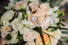 Silver earrings with diamonds bride lying on the bridal bouquet with white roses. Royalty Free Stock Photography