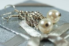 Silver earrings with gems and pearls on shiny gift box royalty free stock photo