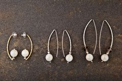 Silver earrings moonstone set asphalt background stock images