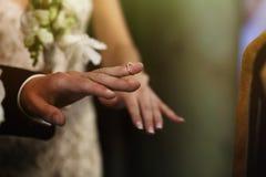 Silver elegant wedding ring on groom finger in church closeup.  Stock Image