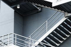 Silver emergency stairs in gray building stock photography