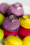 Silver engagement ring and wedding rings on macaroons. Silver engagement ring and wedding rings on colorful Stock Image