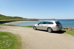 Silver estate car in sunny panoramic view with road, beach, sea. Silver estate, variant, station wagon, car parked by side of road. Blue sea, sandy beach, & stock photos
