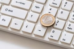 Silver euro coin with a gilded border close-up lies on the key with the number one. White computer keyboard. Shareholders on the. Silver euro coin with a gilded royalty free stock image