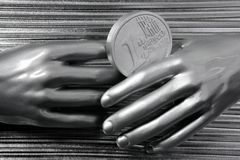 Silver euro coins in futuristic robot hands Stock Image