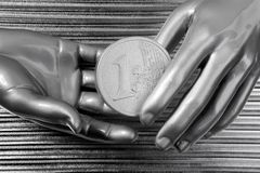 Silver euro coins in futuristic robot hands Royalty Free Stock Image