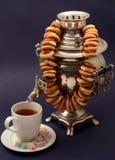 Silver för samovar för svart te gammal på mörk bakgrund med bagelsötsaker Arkivfoton