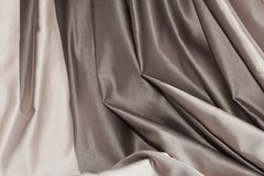 Silver fabric folds, background. Elegant silver fabric folds emphasized by the playing between light and darkness, background Royalty Free Stock Photography