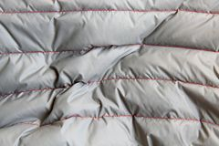 Silver fabric quilted with red threads smooth lines crumpled can serve as a background royalty free stock photography