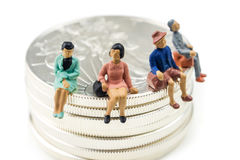 Silver fever. Group of people miniature figurines sitting on silver american eagle coins on white background stock photos