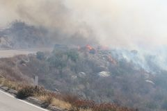 The Silver Fire In Beaumont California ~ 2013 ~ Fire Burning Along Road With Car Driving Thru Stock Photography
