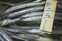 Silver fish for sale in Japan. With Japanese text on a piece of wood Stock Photography