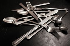 Silver flatware set afterparty cleaning. Silver cutlery on black background. Dishes cleaning after a party concept Royalty Free Stock Images