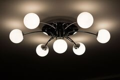 Silver Flush Mount Ceiling Light With Seven White Globe Lights Stock Image