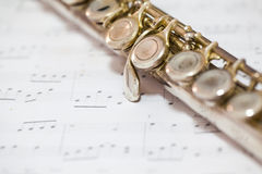 Silver flute. On an ancient music score background Royalty Free Stock Photos