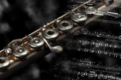 Silver flute  on a music score. Silver flute instrument resting on a music score Royalty Free Stock Images