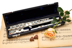 Silver flute, yellow rose and chocolate hearts  on an ancient music score. Background Stock Photography