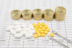 Silver forceps and pill with step pile of gold coins Royalty Free Stock Photo