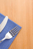 Silver fork and knife as utensils at napkin on wood Royalty Free Stock Photo