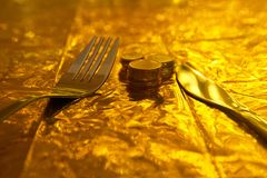 Silver fork and knife with coin money on gold background concept. Silver fork and knife with coin money on gold dinner background concept of business financial royalty free stock images