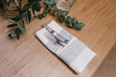 Silver Fork and Knife Inside Gray and White Table Napkin on Table royalty free stock image