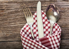 Silver fork, knife and spoon as utensils. On wooden table Stock Images