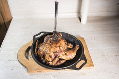 A silver fork is stuck in a roasted fat chicken, which lies in a frying pan on a wooden cutting board on a light background Stock Photos