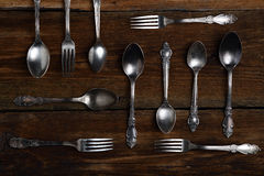 Silver forks and spoons on wooden background Royalty Free Stock Photos