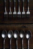 Silver forks and spoons on wooden background Stock Images
