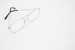 Silver frame glasses at corner on white background Royalty Free Stock Photos