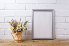 Silver frame mockup with chamomile and grass in golden pitcher. Silver frame mockup with white field chamomile and grass in golden pitcher vase. Empty frame mock Royalty Free Stock Photography