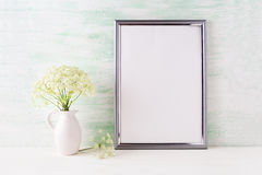 Silver frame mockup with delicate wild field flowers in pitcher Stock Photos