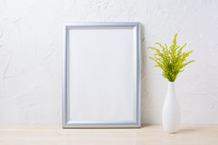 Silver frame mockup with ornamental grass in exquisite vase. Empty frame mock up for presentation artwork Stock Photography