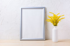 Silver frame mockup with ornamental yellow flowering grass in va. Se. Empty frame mock up for presentation artwork Royalty Free Stock Photos