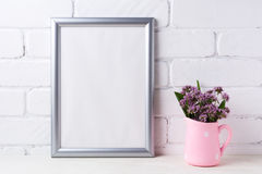 Silver frame mockup with purple flowers in pink rustic pitcher. Silver frame mockup with purple field flowers in polka dot pink rustic pitcher vase. Empty frame Stock Images