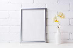 Silver frame mockup with soft yellow orchid in vase Stock Photos