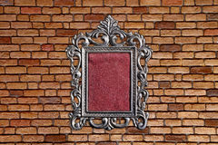 Silver frame on old brick wall. Background Stock Photo