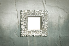 Silver frame on rough wall. A silver colored square ornate frame mounted on a rough textured wall. Add your own picture Stock Photography