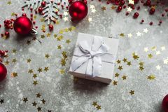 Silver gift with bow on grey snowy background with red Christmas balls and gold confetti stars