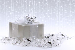 Silver Gift Box. An elegant silver gift box nestled in silver and crystal garlands with sparkles and stars in background Stock Photos