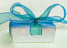 Silver Gift Box With Blue Bow On Green Tablecloth. Shiny silver gift box with blue/green bow Stock Photos