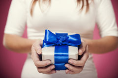 Silver gift box with blue bow. Woman hands holding silver gift box with blue bow Royalty Free Stock Photo