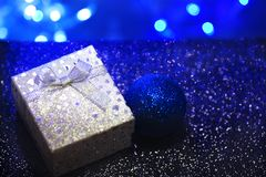 Silver gift box with a bow and hearts on a dark blue blurred background stock photos