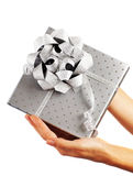 Silver gift box with hands Royalty Free Stock Photos